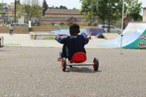 Black boy riding tricycle